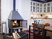 Open plan design kitchen with a wood burning stove next to a dining area