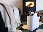 White leather bag in front of a wood burning stove with fire