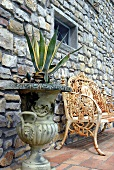 Agave in an antique plant container and rusty bench in front of natural stone facade