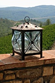 Lantern on a stone wall with a view of a Mediterranean landscape