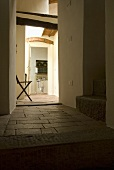 Stool in the entryway of a country home with terracotta tile and a view through an open door