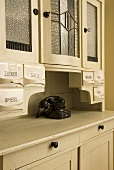 White crockery cupboard with porcelain storage containers and old fashioned telephone
