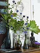 Purple flowers in assorted vases next to a statue of the Buddha on a wooden shelf