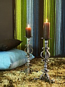 Antique metal candle holders with burning candles and pillows on a flokati rug