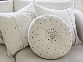 White embroidered pillows on a sofa