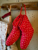 Red slippers made from fabric with a heart print on wardrobe hooks
