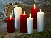 Pine bough in front of burning red and white candles