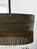 Detail of a black hanging lamp with fringe