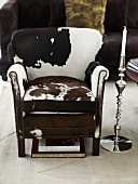 Reading chair with a hide cover and floor candleholder out of chrome