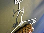 Weisser Metallkleiderbügel am Wandhaken