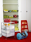 A rolling cabinet, a bag and a red step stool in front of a wardrobe with an open door