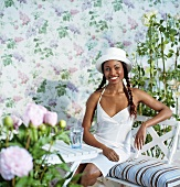 Woman dressed in white on a garden bench in front of a backdrop with flowers and rose trees on it