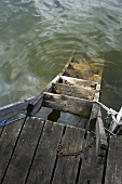 Wooden ladder in water, tied to a jetty