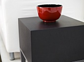 Shiny, red ceramic bowl on a square side table