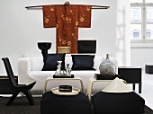 Black chair and seat cushion with white sofa around a side table with a kimono hanging on the wall