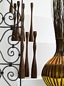 Collection of wooden sculptures next to decorative wrought iron with a floral design and willow basket with colorful fabric strips