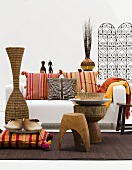 Pillows in front of a floor vase and rustic stool in front of a white sofa with colorful pillows