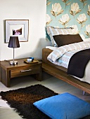 Corner of a bedroom with night stand made of dark wood and a wall hanging with a floral design in front of a bed