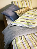 Bed with strip bed linen and decorative pillows