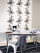 Chair and dining table with metal frame in front of a wall hanging with black and white Asian design