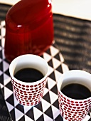 Filled coffee mugs and a red tin on a black and white surface
