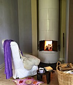 A cosy coffee break in front of a wood burning stove with white tiles and an open door with a view of the crackling fire