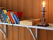 Candlestick with lighted candle and books on a shelf in front of a wood paneled wall
