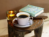 A cup of coffee, a book and a tea light on a rustic wooden stool