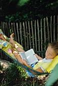 A girl lying in a hammock reading a book in a garden
