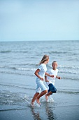 A girl and a boy running along a beach