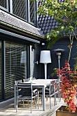 Hausecke mit Terrassenplatz, möbliert mit Tisch, Stühlen und einer Stehlampe