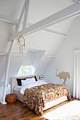 Dachraum und Konstruktion weiss gestrichen, unter dem Fenster ein Doppelbett