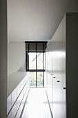 Schmaler Raum mit weißem Sideboard und weißem Hochschrank an den Längsseiten, ein raumhohes Fenster stirnseitig