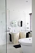 Weisses Badezimmer mit freistehenden Waschtischen und Unterbau, runde Spiegel an der Wand und schwarze Handtücher