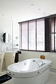 A free-standing bathtub with a circumferential stainless steel bar in a white bathroom with a large window bank