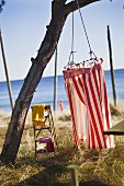 A red and white striped changing cabin hanging from a tree on a beach with a sea view