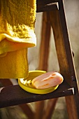 Soap in a yellow bowl and a towel on a wooden ladder
