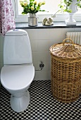 A toilet and a wash basket in a bathroom with a chess board pattern