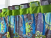 A colourful curtain with a green ribbon