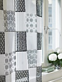 Curtains made of a black and white patchwork-patterned fabric