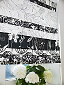 A black and white patterned blind and a flower pot on a window sill