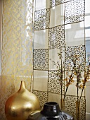 A golden vase and a patterned, transparent curtain