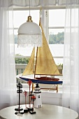 A white ceiling lamp above a table next to a window and a model boat displayed on a window sill