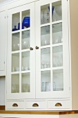 White lacquer crockery cupboard with glass panes separated by glazing bars
