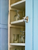 A metal door knob on a blue cupboard with an open door