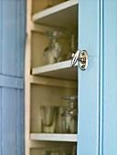 A metal door knob on a blue cupboard with an open door