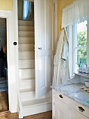 An anteroom in a country house with a chest of drawers and a white wooden door leading to a flight of stairs