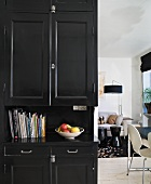 A black kitchen cupboard and view into a living room