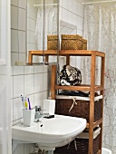 A wash basin and baskets on a wooden shelf in a bathroom