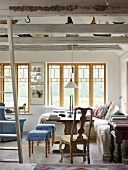 A living room with wooden beams in a country house with a dining area in front of a window